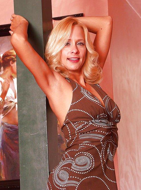 Привлекательная блондинка в трусиках делает селфи у лестницы