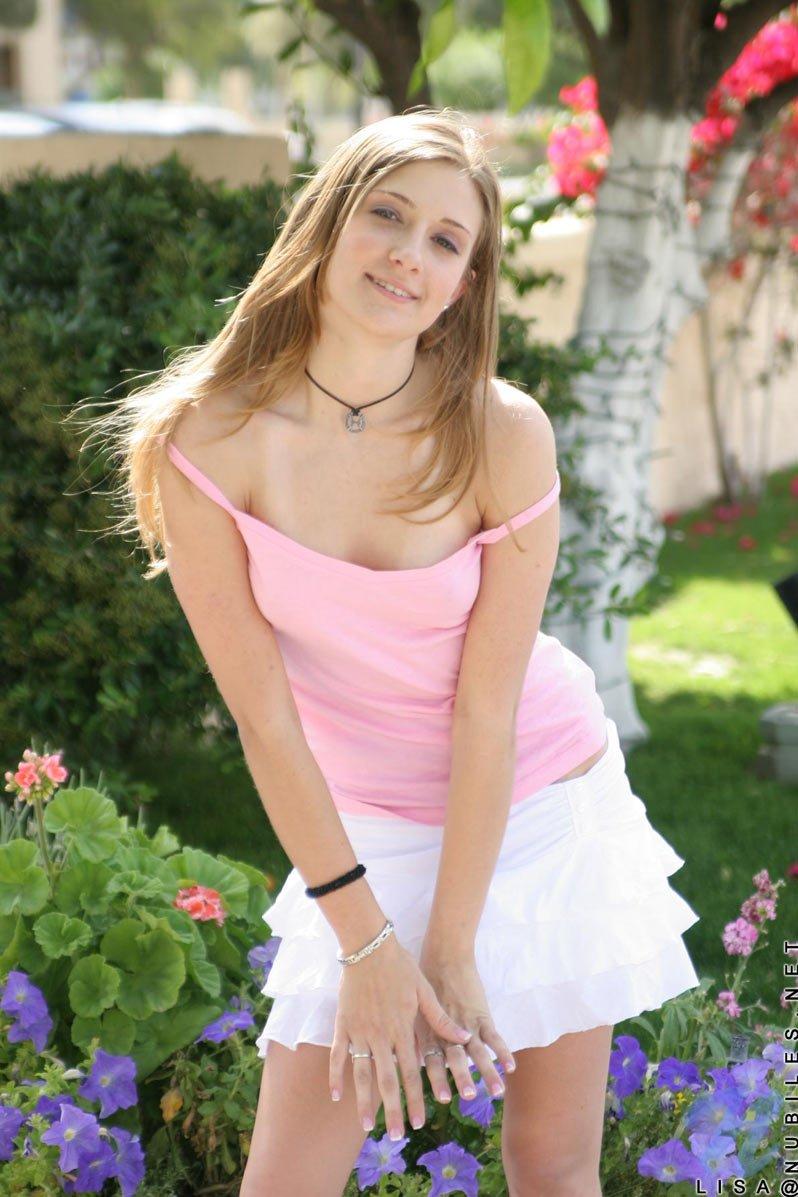 Эффектная красотка в розовом топике и белой юбке Lisa Nubiles снимается на поляне