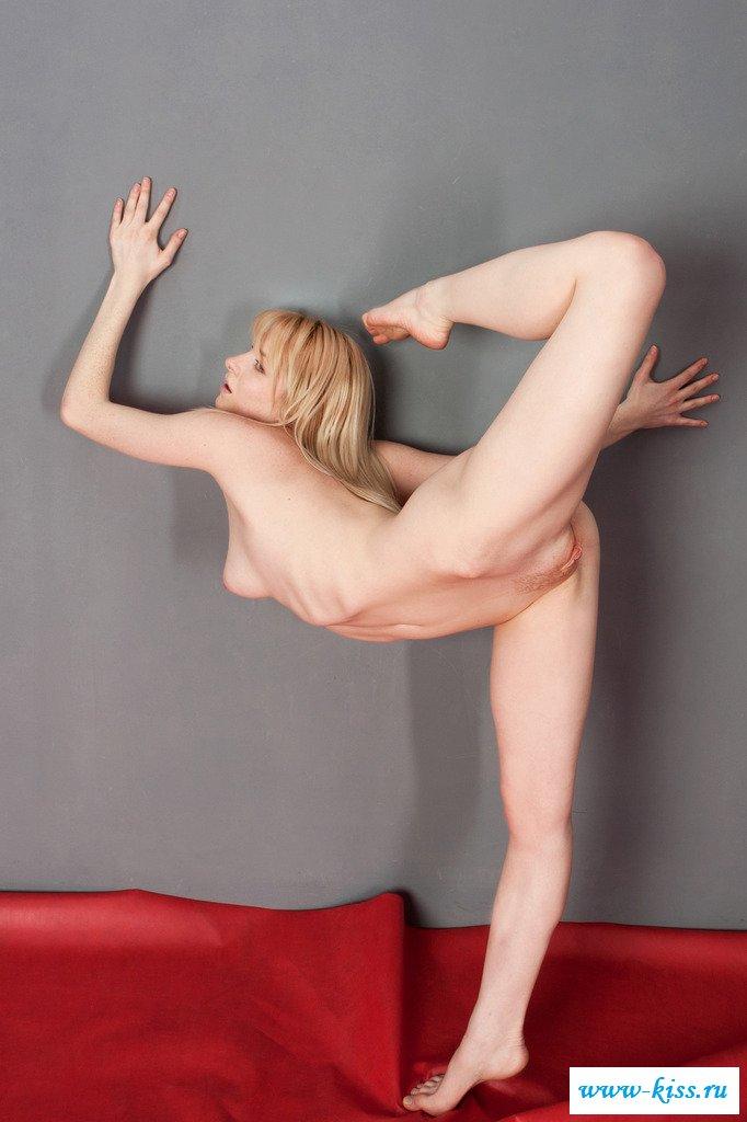 Обнаженная гимнастка на шпагате задирает ноги у табурета